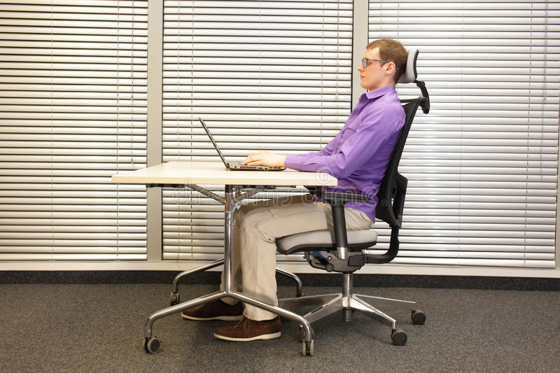 Correct sitting position at workstation. man on chair working with laptop. Profile view royalty free stock images