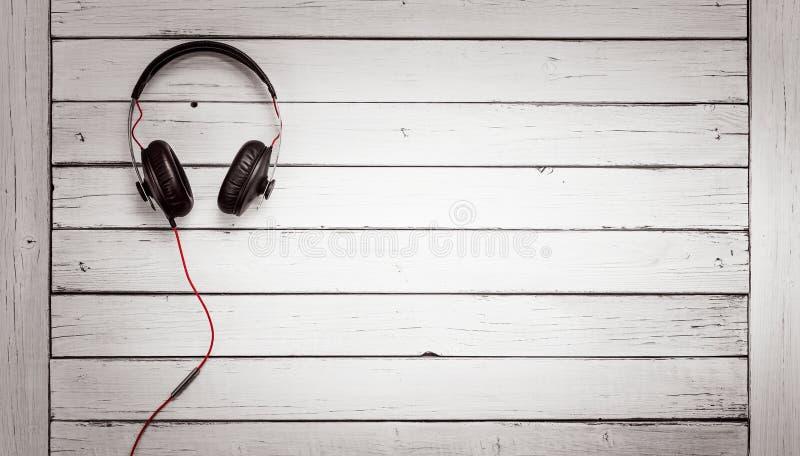 Correcte oortelefoons die op houten rustieke achtergrond liggen royalty-vrije stock afbeelding