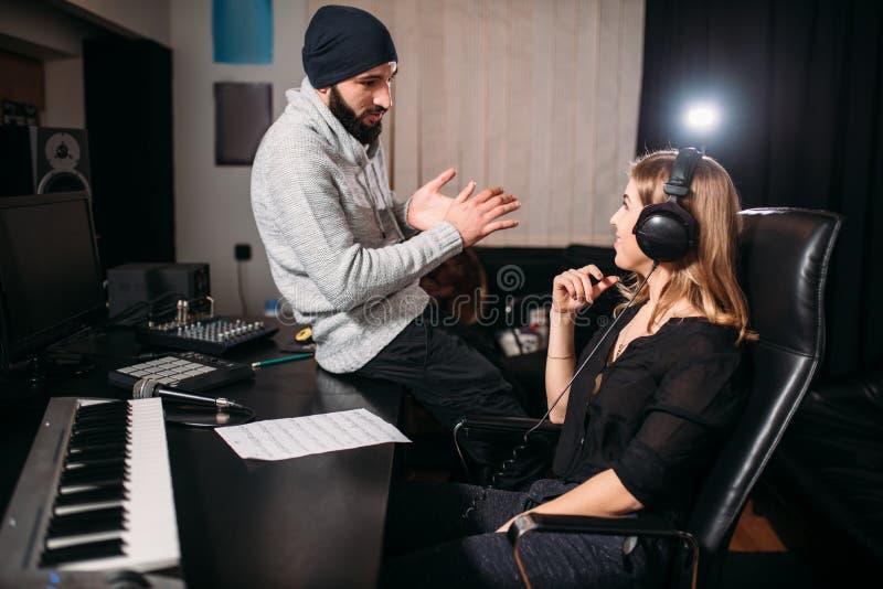 Correcte producent met vrouwelijke zanger in muziekstudio stock afbeeldingen
