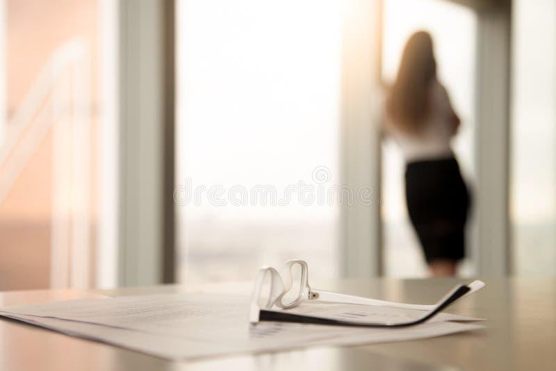 Correctieve glazen voor lezing op bureau, vrouwelijk silhouet bij bac royalty-vrije stock foto's