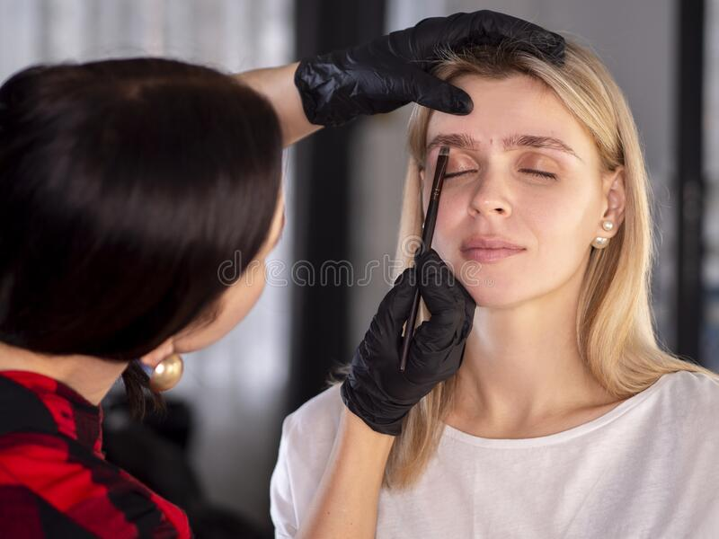 Correcting with a brush new eyebrow shape. Young woman on a cosmetic procedure. Correcting with a brush new eyebrow shape. Young women on a cosmetic procedure stock images