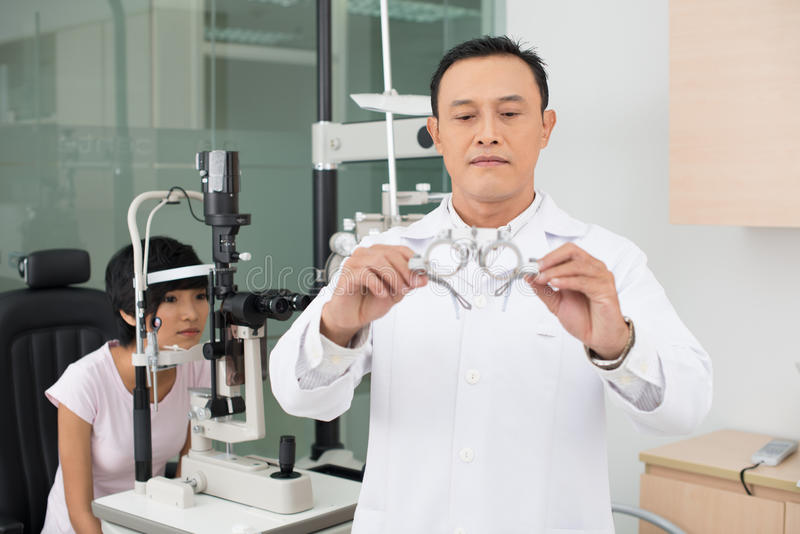 Correcting eyesight. Mature optician reaching out glasses to female patient sitting on background stock photos