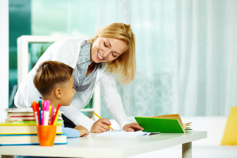 Correcting mistakes. Portrait of smart tutor with pencil correcting mistakes in pupil�s notebook royalty free stock photo