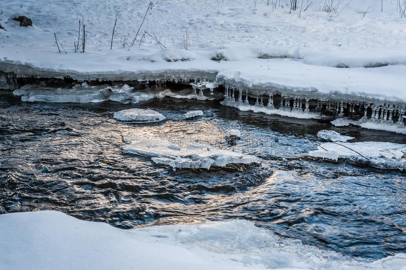 Correction dégelée par ressort dans la glace de la rivière Glace et neige congelées par le côté de rivière image stock