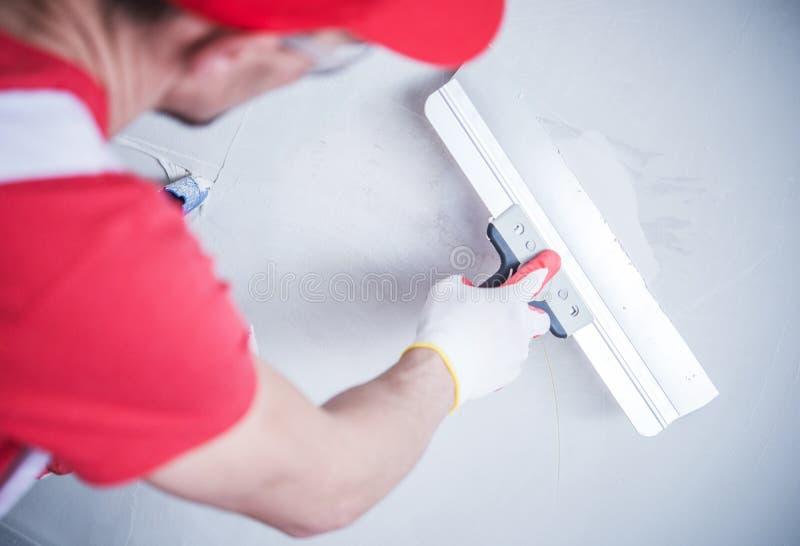 Correction de cloison sèche par le travailleur photographie stock