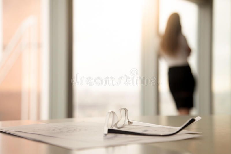 Corrective glasses for reading on desk, female silhouette at bac. Corrective fashionable reading glasses in white frame lying on documents on desk, female royalty free stock photos