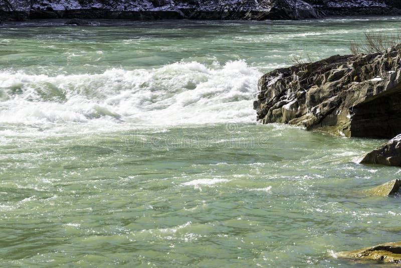 A corredeira do rio com branco acena o fluxo, a neve e o gelo no riv rochoso imagens de stock royalty free