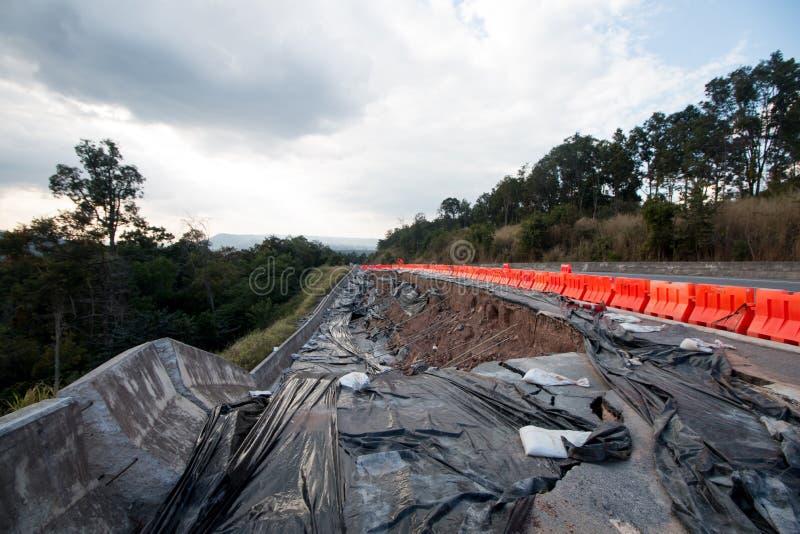 Corrediça da terra na estrada asfaltada em Tailândia, fotos de stock
