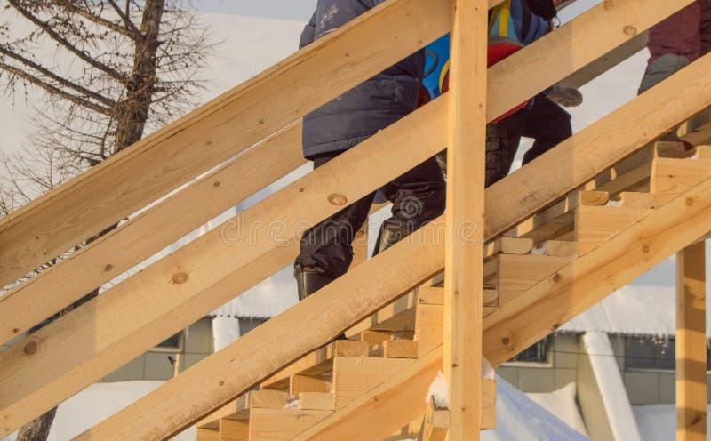 A corrediça de madeira para crianças no inverno, as crianças com pequenos trenós e a tubulação escalam o monte, divertimento no N imagem de stock
