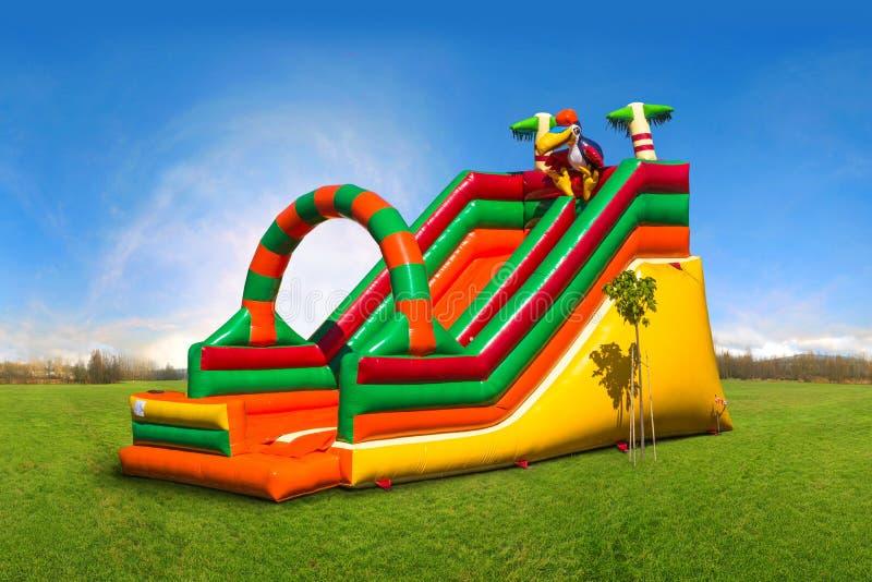 Corrediça inflável colorida enorme no campo de jogos fotografia de stock