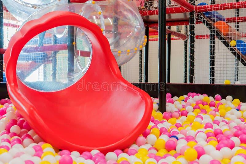 corrediça plástica com as bolas coloridas para o kid& x27; campo de jogos de s fotografia de stock