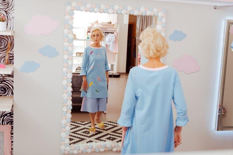 Corrediças vestindo aposentadas à moda do amarelo da mulher e vestido azul imagens de stock