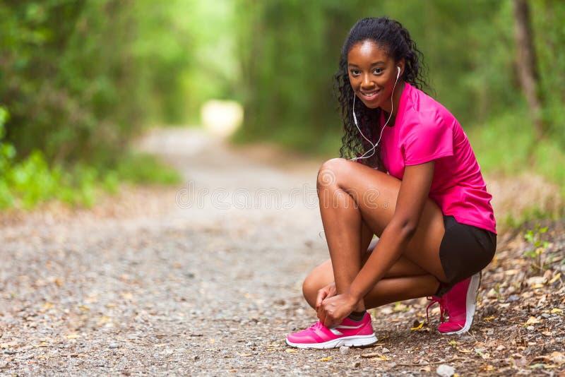 Corredor afroamericano de la mujer que aprieta el cordón de zapato - aptitud, el PE imagen de archivo