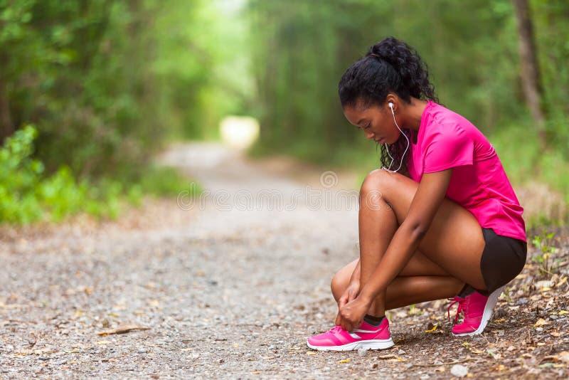 Corredor afroamericano de la mujer que aprieta el cordón de zapato - aptitud, el PE fotos de archivo libres de regalías