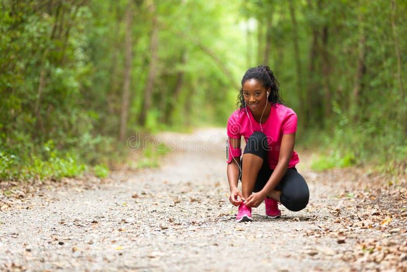 Corredor afroamericano de la mujer que aprieta el cordón de zapato - aptitud, el PE fotografía de archivo libre de regalías