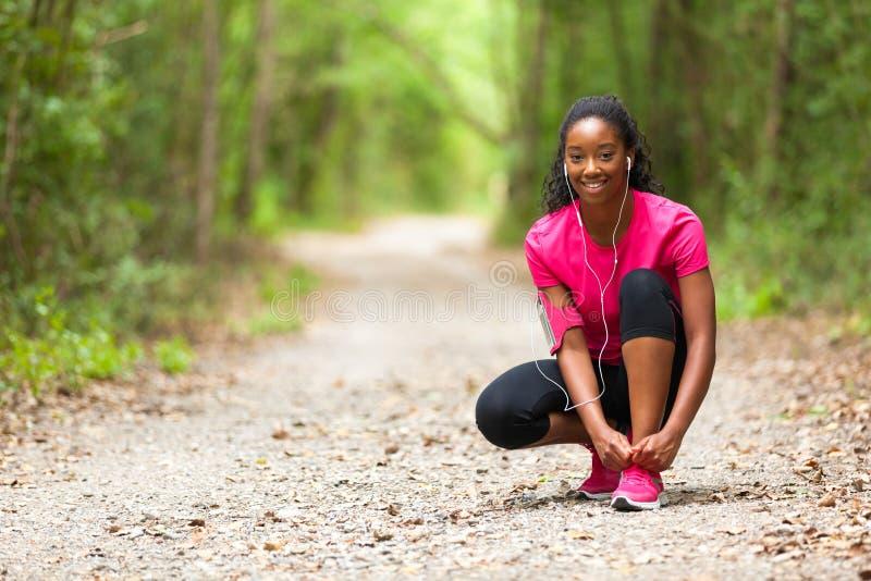 Corredor afroamericano de la mujer que aprieta el cordón de zapato - aptitud, el PE foto de archivo