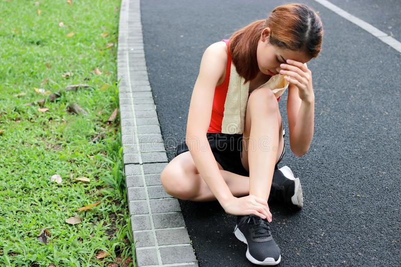 Corredor asiático novo da mulher da aptidão que sofre de tornozelo torcido quebrado Conceito running do acidente de ferimento imagem de stock royalty free
