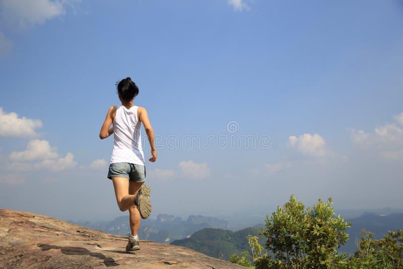 Corredor asiático novo da mulher que corre no pico da rocha da montanha imagem de stock royalty free