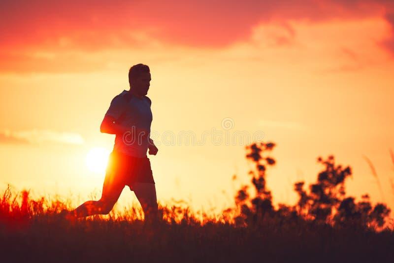 Corredor atlético en la puesta del sol imagen de archivo