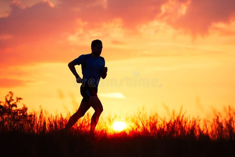 Corredor atlético en la puesta del sol imagen de archivo libre de regalías