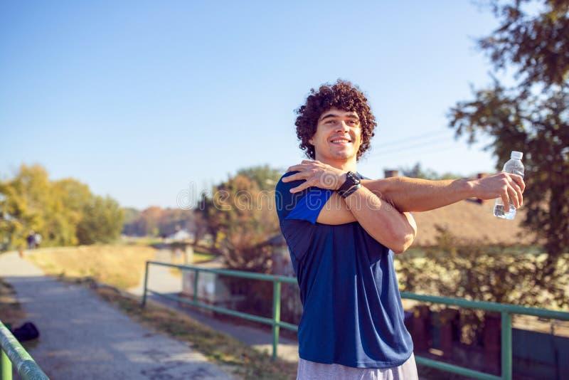 Corredor atlético que faz esticando o exercício, preparando-se para o exercício imagens de stock royalty free