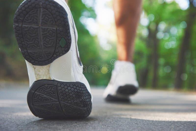 Corredor através dos campos exterior no conceito para o exercício, a aptidão e o estilo de vida saudável Feche acima dos pés do c imagens de stock