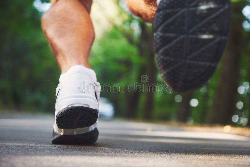 Corredor através dos campos exterior no conceito para o exercício, a aptidão e o estilo de vida saudável Feche acima dos pés do c foto de stock royalty free