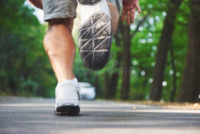 Corredor através dos campos exterior no conceito para o exercício, a aptidão e o estilo de vida saudável Feche acima dos pés do c fotografia de stock