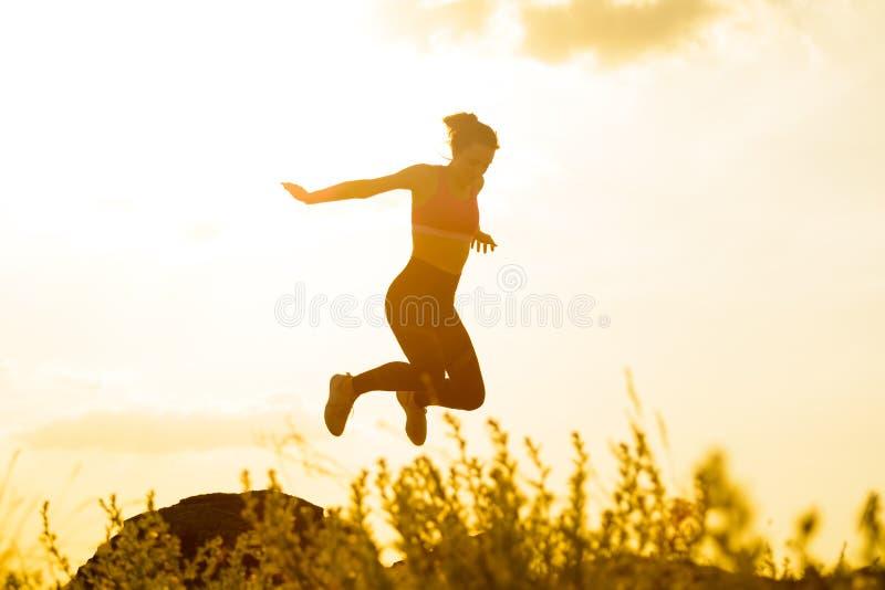 Corredor bonito da mulher que salta da rocha na fuga de montanha no por do sol quente do verão Esporte e estilo de vida ativo foto de stock royalty free