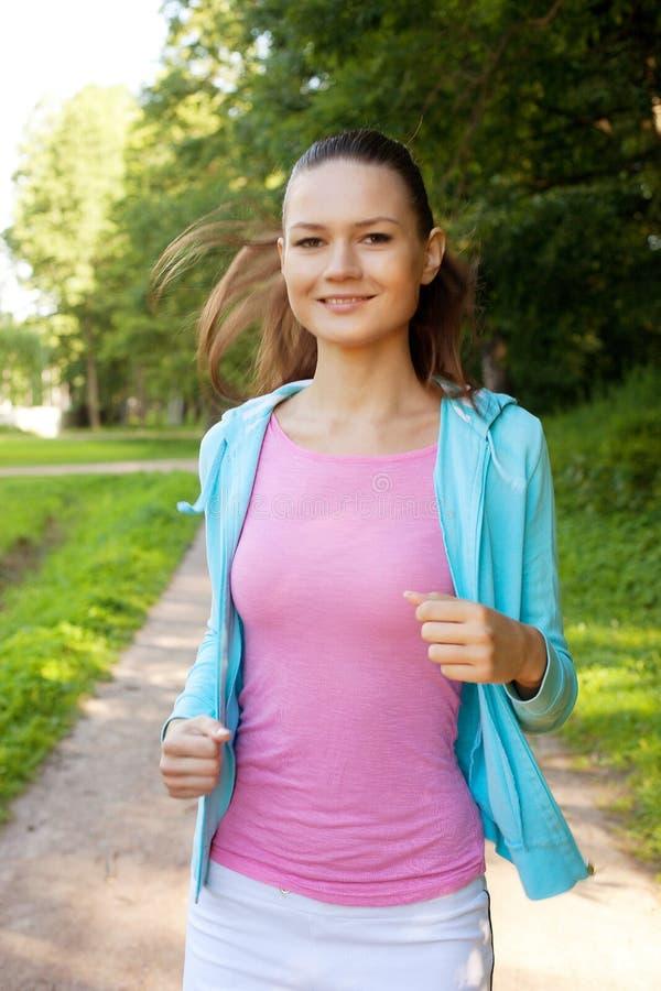 Corredor bonito de la chica joven en el bosque. imagenes de archivo