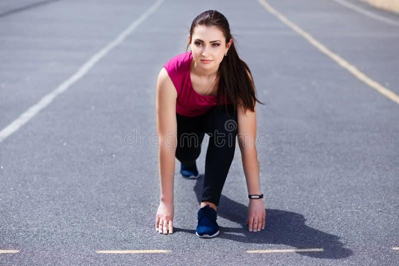Corredor bonito joven de la mujer del ajuste en el comienzo en el racet atlético imágenes de archivo libres de regalías