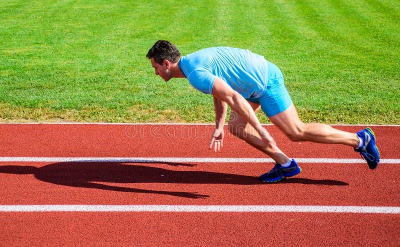 Corredor capturado no movimento imediatamente depois do começo da raça Raça da sprint do corredor no estádio Como começar correr  fotos de stock