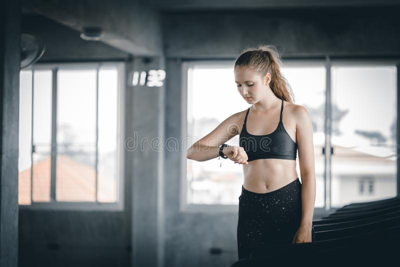 Corredor caucasiano da jovem mulher do ajuste na escada rolante da máquina e vista do exercício esperto do relógio no gym fotografia de stock