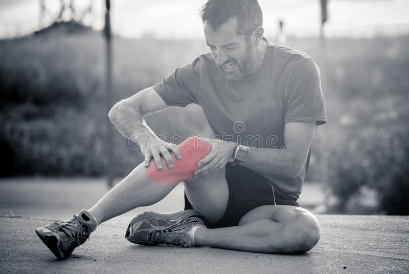 Corredor con lesión del deporte a la rodilla foto de archivo libre de regalías