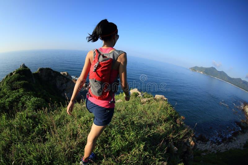 Corredor da fuga da mulher da aptidão na fuga de montanha do beira-mar fotografia de stock royalty free