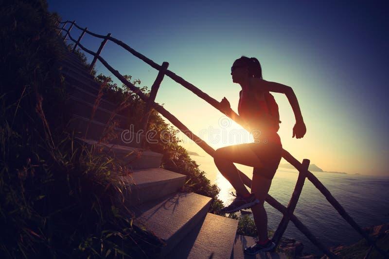 Corredor da fuga da mulher que corre acima em escadas da montanha fotografia de stock royalty free