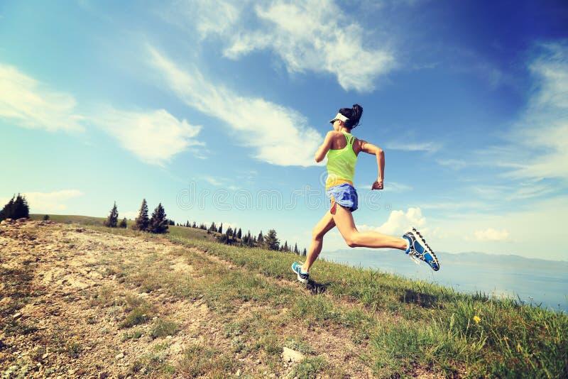 corredor da fuga da mulher que corre no pico de montanha bonito imagem de stock