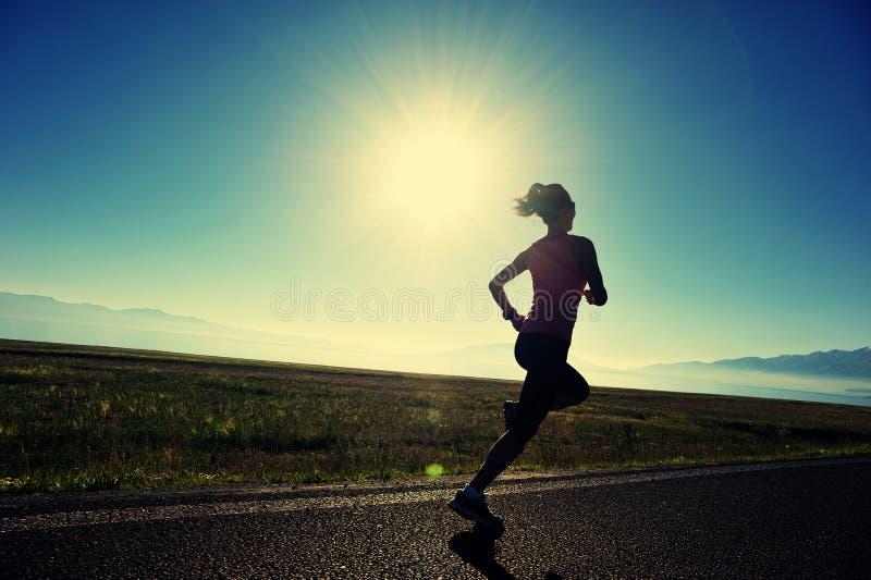 corredor da jovem mulher do estilo de vida que corre na estrada do nascer do sol fotografia de stock