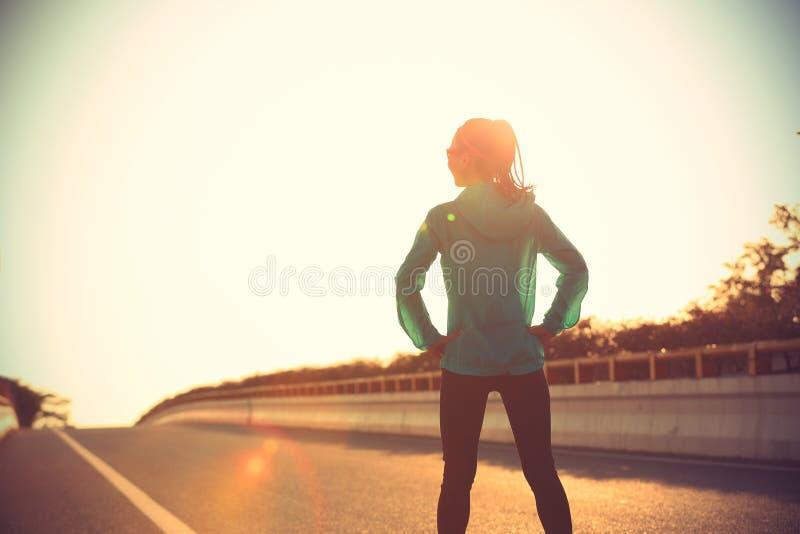 Corredor da jovem mulher que está com suas mãos nos quadris na estrada do nascer do sol imagem de stock royalty free