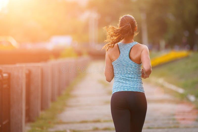 Corredor da jovem mulher que movimenta-se no parque na manhã imagens de stock
