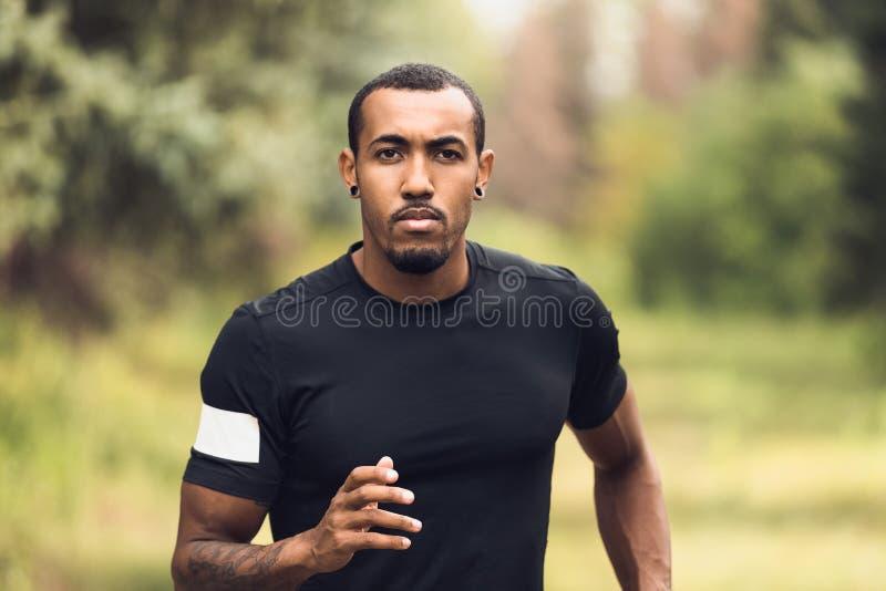 Corredor da manh? Corredor afro-americano que movimenta-se no parque fotos de stock royalty free