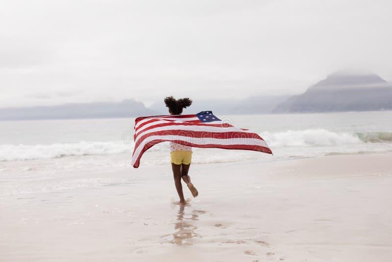 Corredor da menina com a bandeira americana na praia fotos de stock royalty free