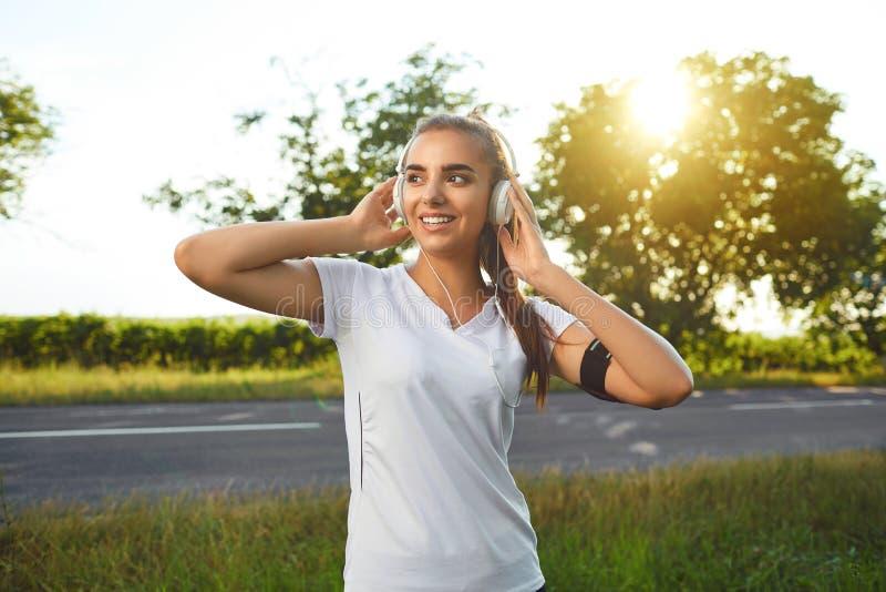 Corredor da menina com os auriculares que descansam antes de movimentar-se na estrada imagem de stock royalty free