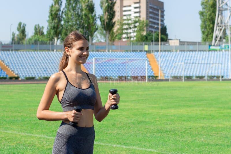 Corredor da moça com pesos nas mãos no estádio Esportes e conceito saudável foto de stock