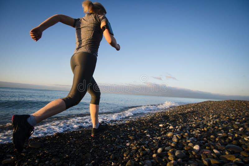Corredor da mulher adulta que corre no beira-mar do nascer do sol Estilo de vida saudável imagem de stock royalty free