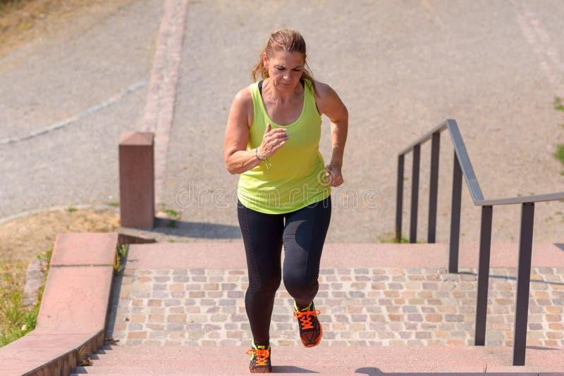 Corredor da mulher ao escalar escadas durante o exercício imagem de stock