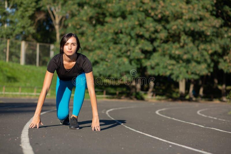 Corredor da mulher do ajuste na posição começar pronta para a sprint Espaço vazio fotos de stock royalty free