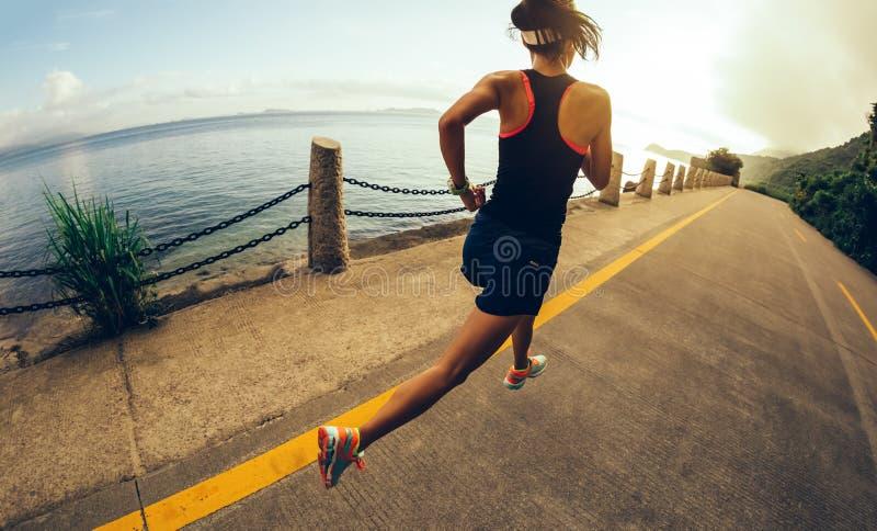 Corredor da mulher na fuga do beira-mar fotos de stock