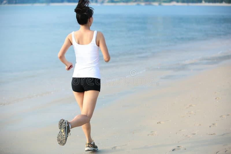 Corredor da mulher na praia imagens de stock