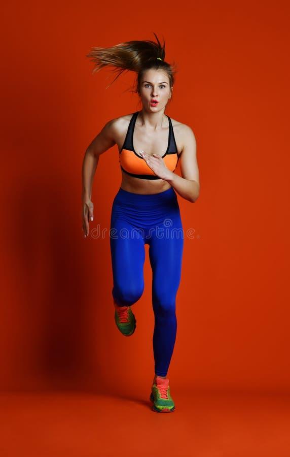 Corredor da mulher na silhueta isolada no fundo vermelho movimento dinâmico Esporte e estilo de vida saudável fotografia de stock